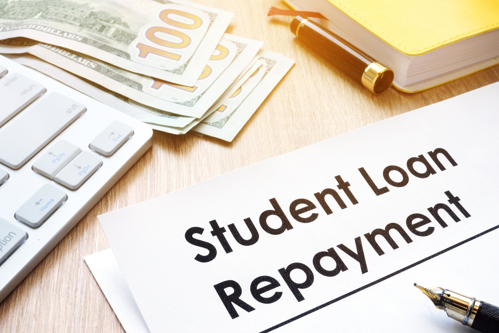 A calculator, hundred dollar bills, a book, and pen all sit beside a paper reading Student Loan Repayment.
