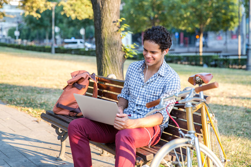 Male Student Working on a Laptop on a Park Bench