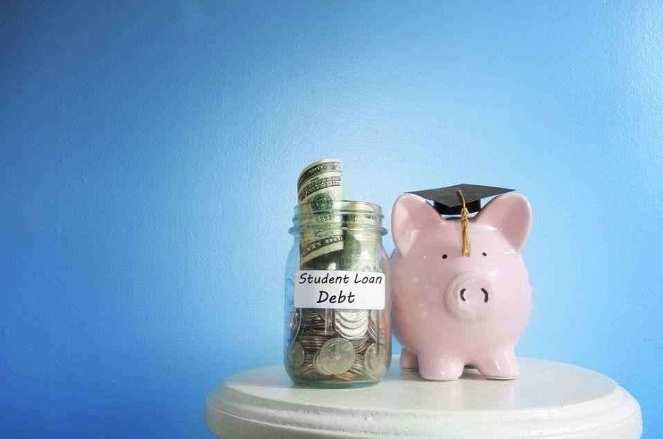 """A jar full of money labelled """"Student Loan Debt"""" stands next to a piggy bank and graduation cap."""