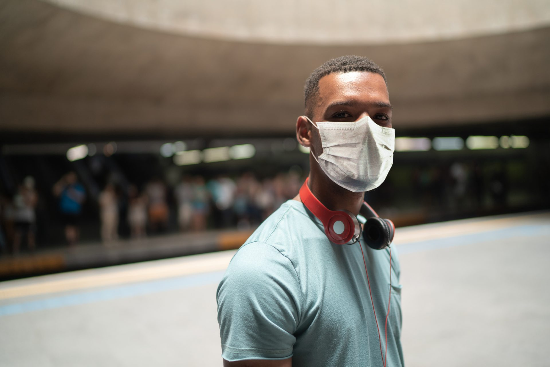 Portrait of a young man using protective mask at metro station.