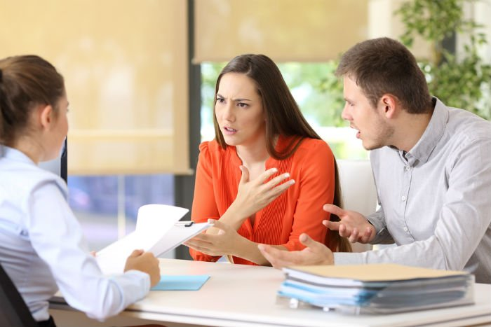 divorced couple discussing student loan debt with a lawyer