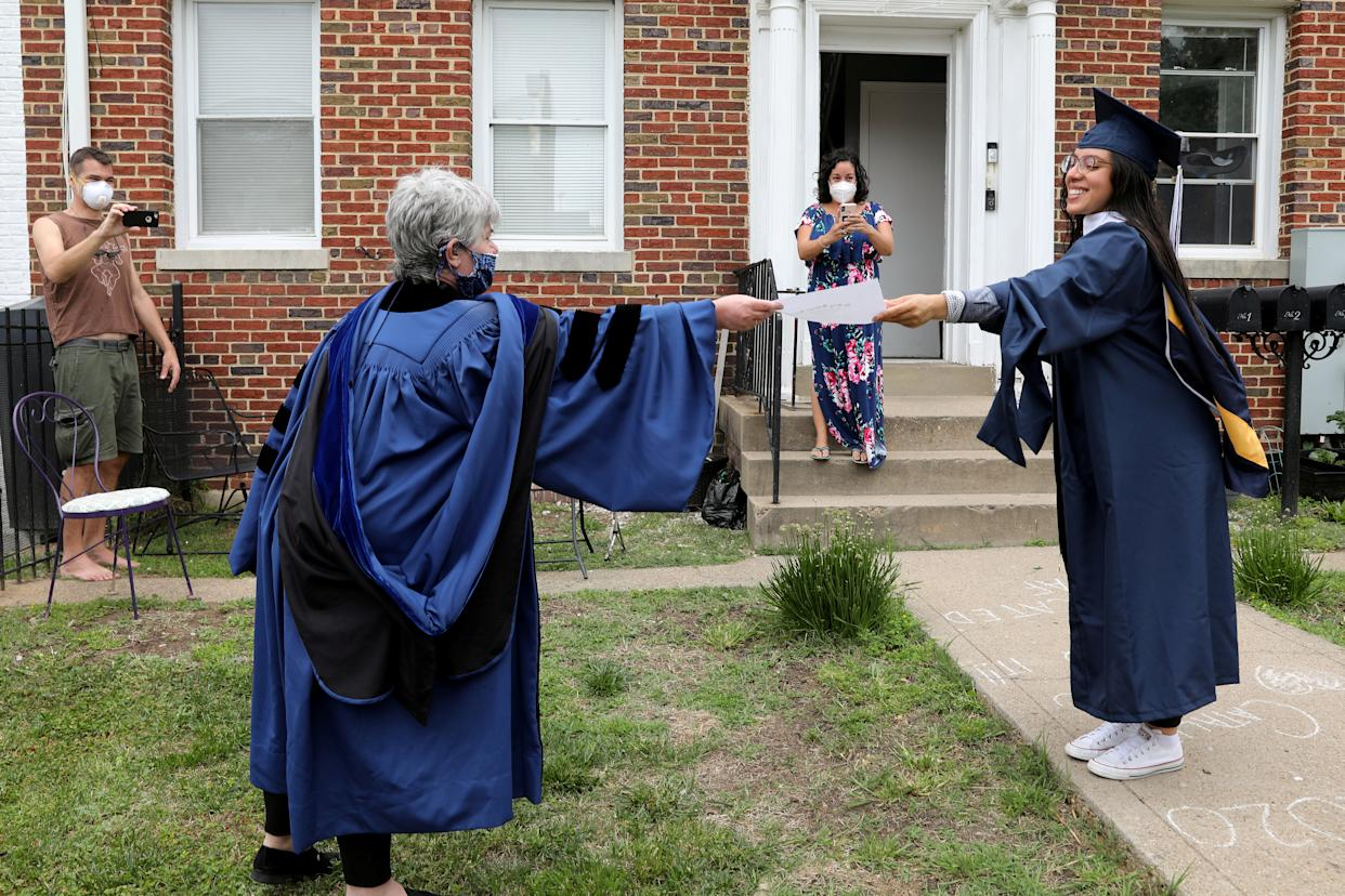 George Washington University graduate Catalina Perez (R) receives a paper copy of her diploma from neighbor Paula Lytle as they keep a social distance at a surprise graduation party for Perez, who completed her undergraduate studies in International Affairs across the span of ten years only to miss her commencement due to the coronavirus disease (COVID-19) outbreak in Washington, U.S., May 17, 2020. REUTERS/Jonathan Ernst     TPX IMAGES OF THE DAY