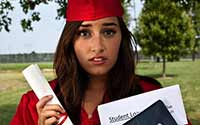 Concerned, female college graduate holding a degree and a student loan bill.