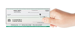 A photo showing a hand holding a check to signify paying for college and the differences between a grant and a loan when it comes to financial aid