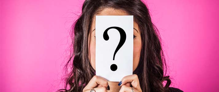 girl holding question mark card